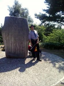pipper vor dem Gedenkstein des ersten Pfadfinderlagers auf Brownsea Island